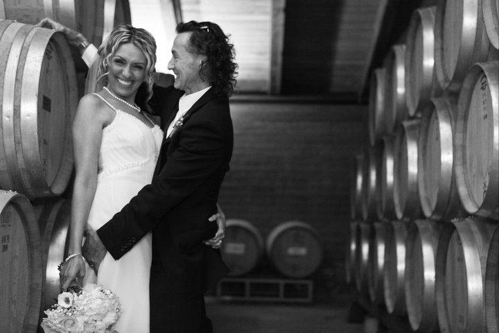 bride groom smile winery barrels hug